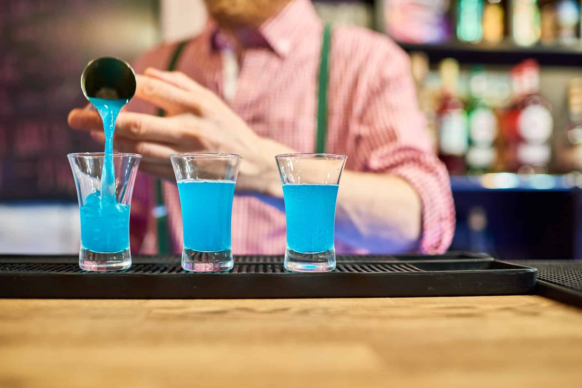 Bartender Pouring Vodka Shots at Bar Counter